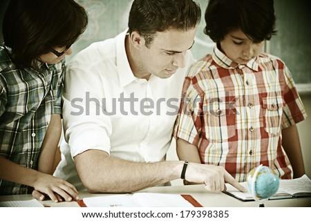 Cheerful kids at school room having education activity with teacher - stock photo