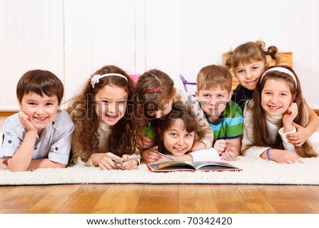 Cheerful kids crowd reading  a book