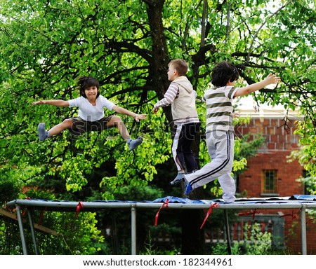 Cheerful kids having fun jumping on trampoline - stock photo