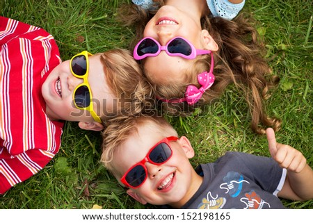 Cheerful kids laying on a grass - stock photo