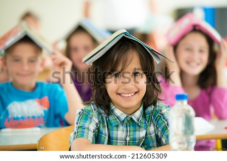 Cheerful kids learning in school classroom - stock photo