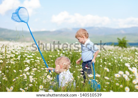 Cheerful kids playing in a field With Insect Net in summer