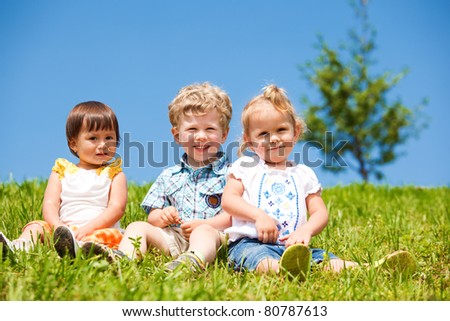 Cheerful kids sit on the green grass - stock photo