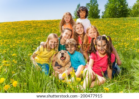 Cheerful kids with dog sitting on the grass