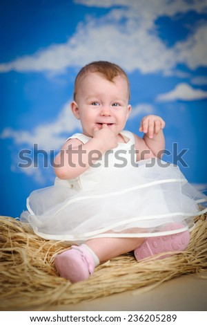 cheerful, kind, smiling child sitting on a straw on a blue sky background - stock photo