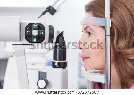 Cheerful lady is getting ophthalmology diopters calibration - stock photo