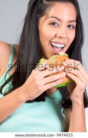 Cheerful Latina girl eating burger during lunch break