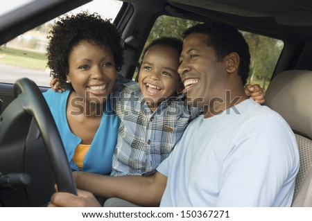 Cheerful little boy and parents sitting in car - stock photo