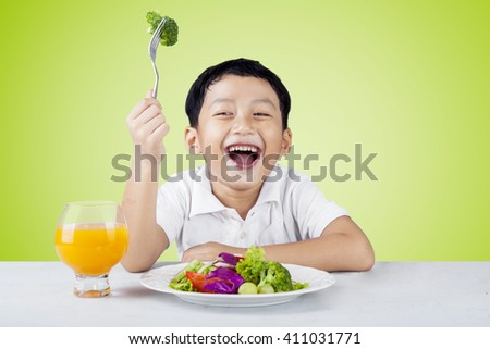 Cheerful little boy eating a plate of fresh vegetables salad and drink a glass of orange juice
