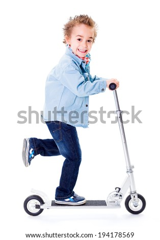 Cheerful little boy going fast with scooter