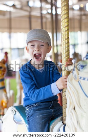 cheerful little boy having fun at the amusement park - stock photo