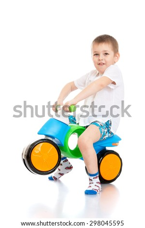 Cheerful little boy in a white shirt and blue shorts riding a two-wheeled plastic bike , he is a biker-Isolated on white - stock photo