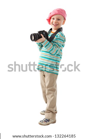 Cheerful little boy is a photographer. He holds the camera. He wears a beret, red scarf, striped sweater and beige pants. - stock photo