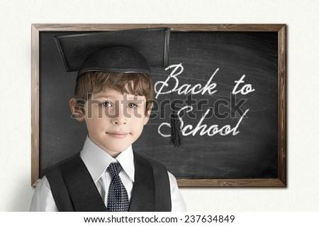 Cheerful little boy on blackboard. Looking at camera - stock photo
