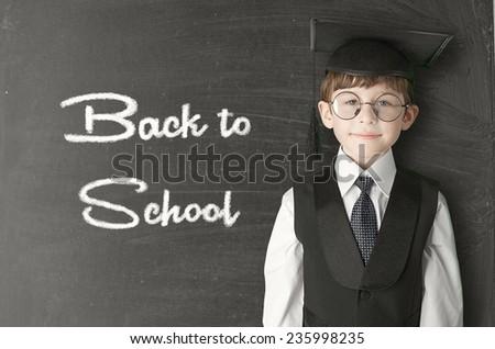Cheerful little boy on blackboard. Looking at camera. School concept - stock photo