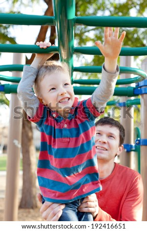 cheerful little boy playing at monkey bars and his father helping him at the playground - stock photo