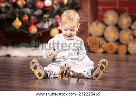 Cheerful little boy playing with his toy animals by Christmas tree - stock photo