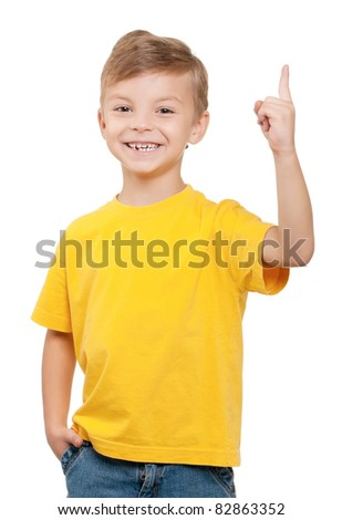 Cheerful little boy pointing up over white background