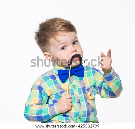 Cheerful little boy posing in studio with paper mustache. Isolated on white background. - stock photo