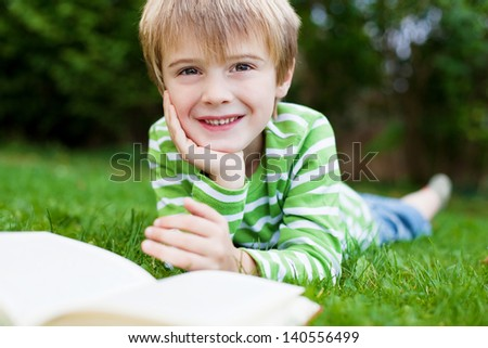 Cheerful little boy reading book on the grass - stock photo