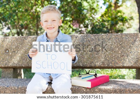 cheerful little boy ready for school holding back to school sign - stock photo