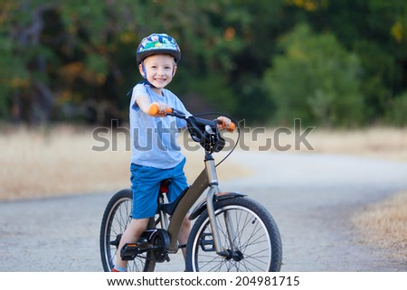 cheerful little boy riding bicycle - stock photo