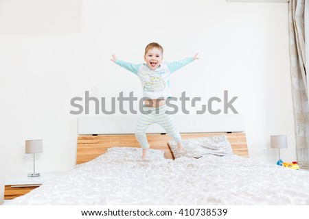 Cheerful little boy showing tongue and jumping on bed at home  - stock photo