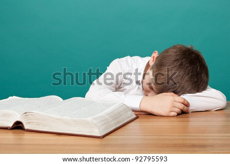 cheerful  little boy sitting at the table  and sleeps next to books. School concept - stock photo
