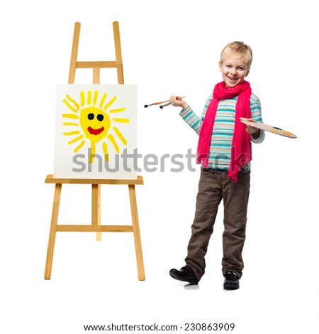 Cheerful little boy standing at the easel. Young artist holds in his hands the palette with paints. He paints the sun. - stock photo