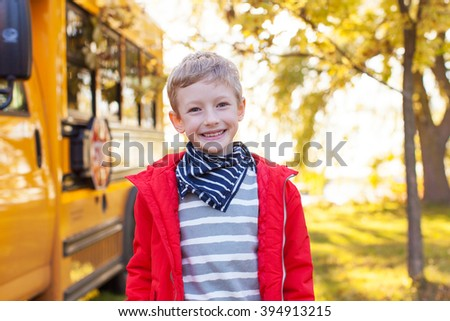 cheerful little boy standing near schoolbus ready to go to school, back to school concept
