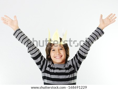 Cheerful little boy with a paper crown on his head - stock photo