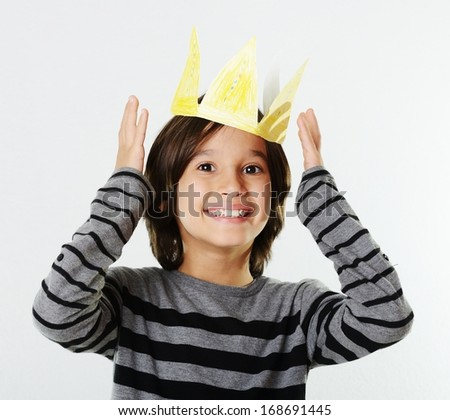 Cheerful little boy with a paper crown on his head