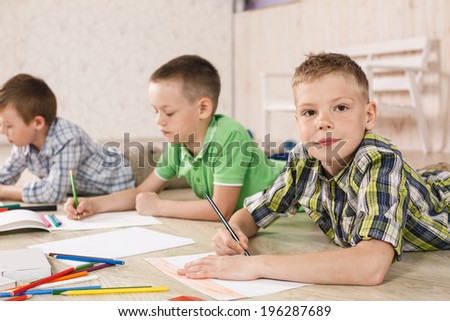 Cheerful little boys are lying on the floor and drawing on paper