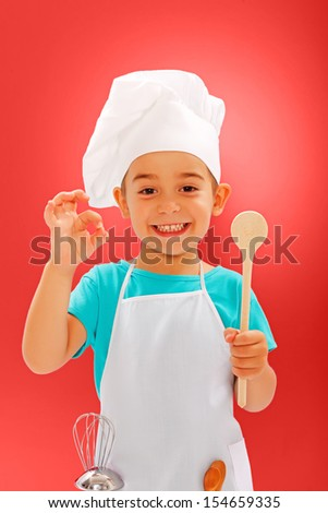 Cheerful little chef showing good taste and wooden spoon - stock photo