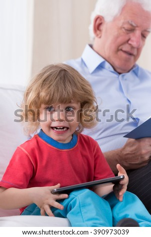 Cheerful little cute boy playing on tablet