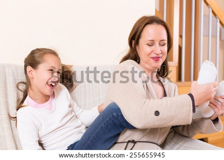 Cheerful little girl and mom playing at domestic interior  - stock photo
