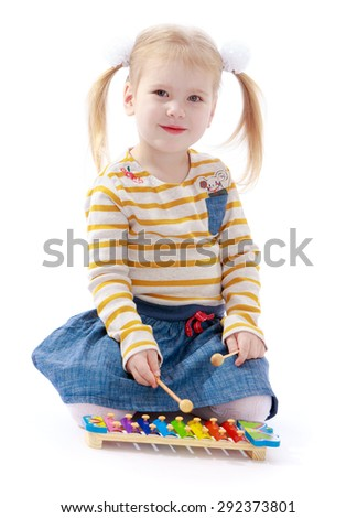 Cheerful little girl blonde girl with ponytails plays xylophone, knocking the hammer sitting on the floor - isolated on white background - stock photo
