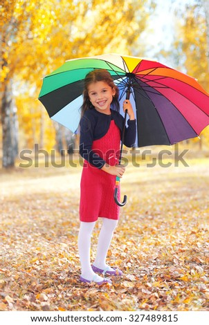 Cheerful little girl child with colorful umbrella in autumn day