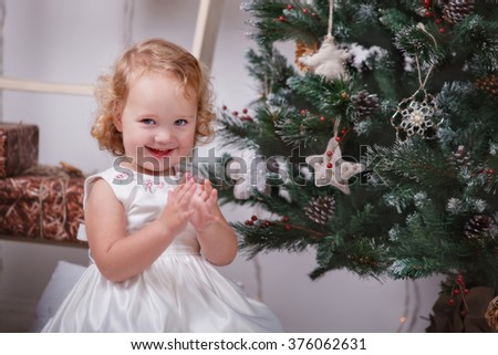 Cheerful little girl clapping hands by the Christmas tree - stock photo