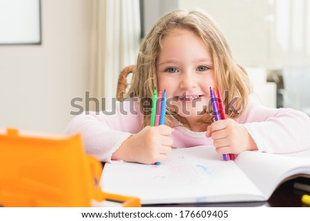 Cheerful little girl colouring at the table at home in kitchen - stock photo