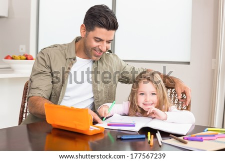 Cheerful little girl colouring at the table with her father at home in kitchen - stock photo