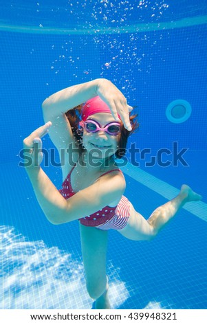 Cheerful little girl dancing under  water in pool. - stock photo