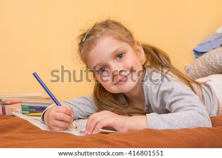 Cheerful little girl draws lying on his stomach with a pencil on paper
