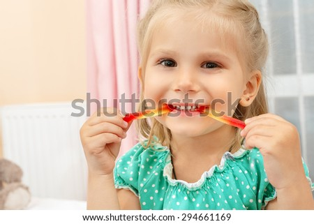Cheerful little girl eating jelly worm - stock photo