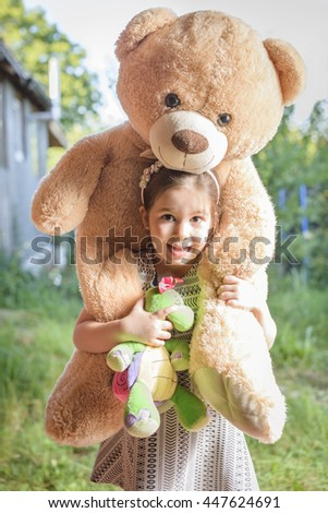 Cheerful little girl giving piggyback ride to her Teddy bear toy outdoors in backyard in a sunny summer day. Beautiful and happy little child with teddy bear on her shoulders - stock photo