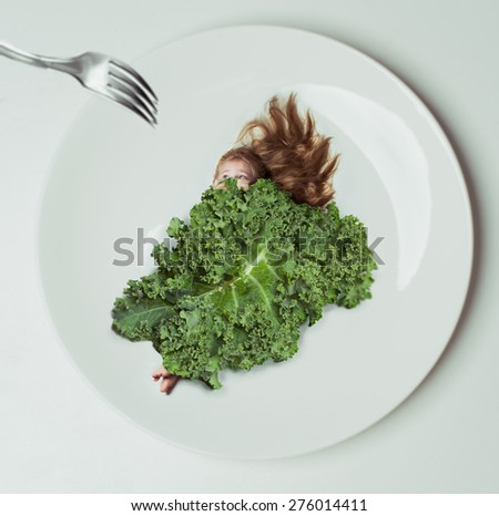Cheerful  little girl holding a head of cabbage/beautiful little with green cabbage (savoy) isolated over white background