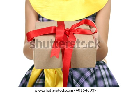 cheerful little girl in a beautiful dress holding a gift with a red ribbon on a white isolated background - stock photo