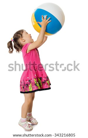 Cheerful little girl in a short pink dress playing with a large inflatable ball. The girl raised the ball with his hands in the top - Isolated on white background - stock photo