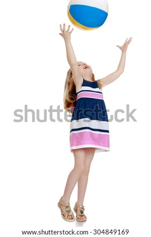 Cheerful little girl in a short summer dress playing with a ball . The girl throws the ball with his hands up-Isolated on white background - stock photo