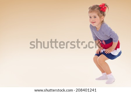 cheerful little girl in a striped dress bent over and holding her hands in her lap.kindergarten, the concept of childhood and joy, teens - stock photo
